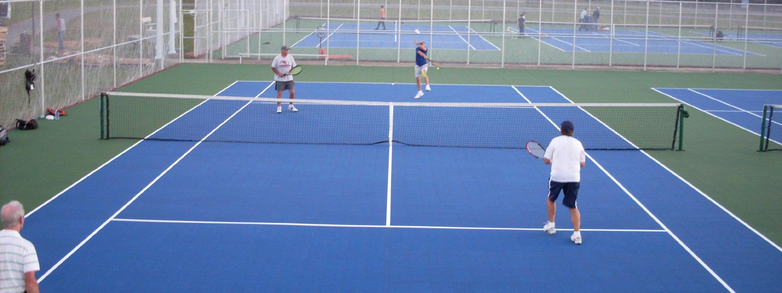 People playing tennis on one of several courts built using Flex Courts premium tiles.
